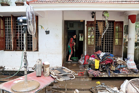 A woman cleans the mud from the entrance of her house following floods in Paravur on Tuesday.