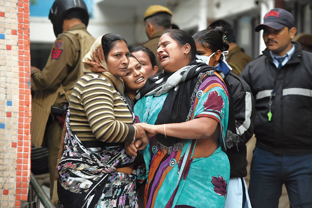 Family members of a man injured in the clash at Guru Teg Bahadur Hospital in New Delhi on Tuesday