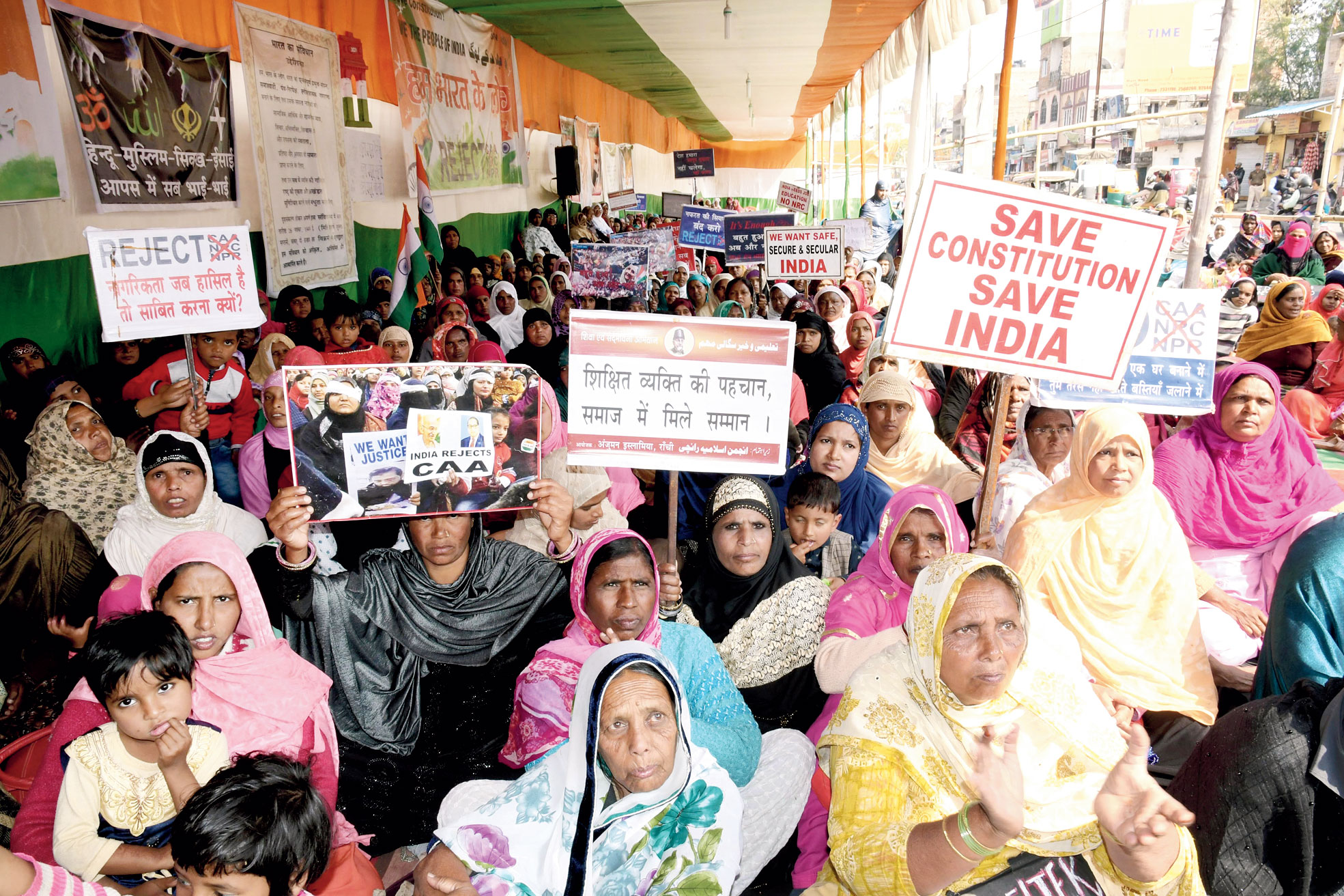 Women hold placards against the citizenship matrix at the indefinite demonstration in front of premise of the Haj House at Kadru in Ranchi
