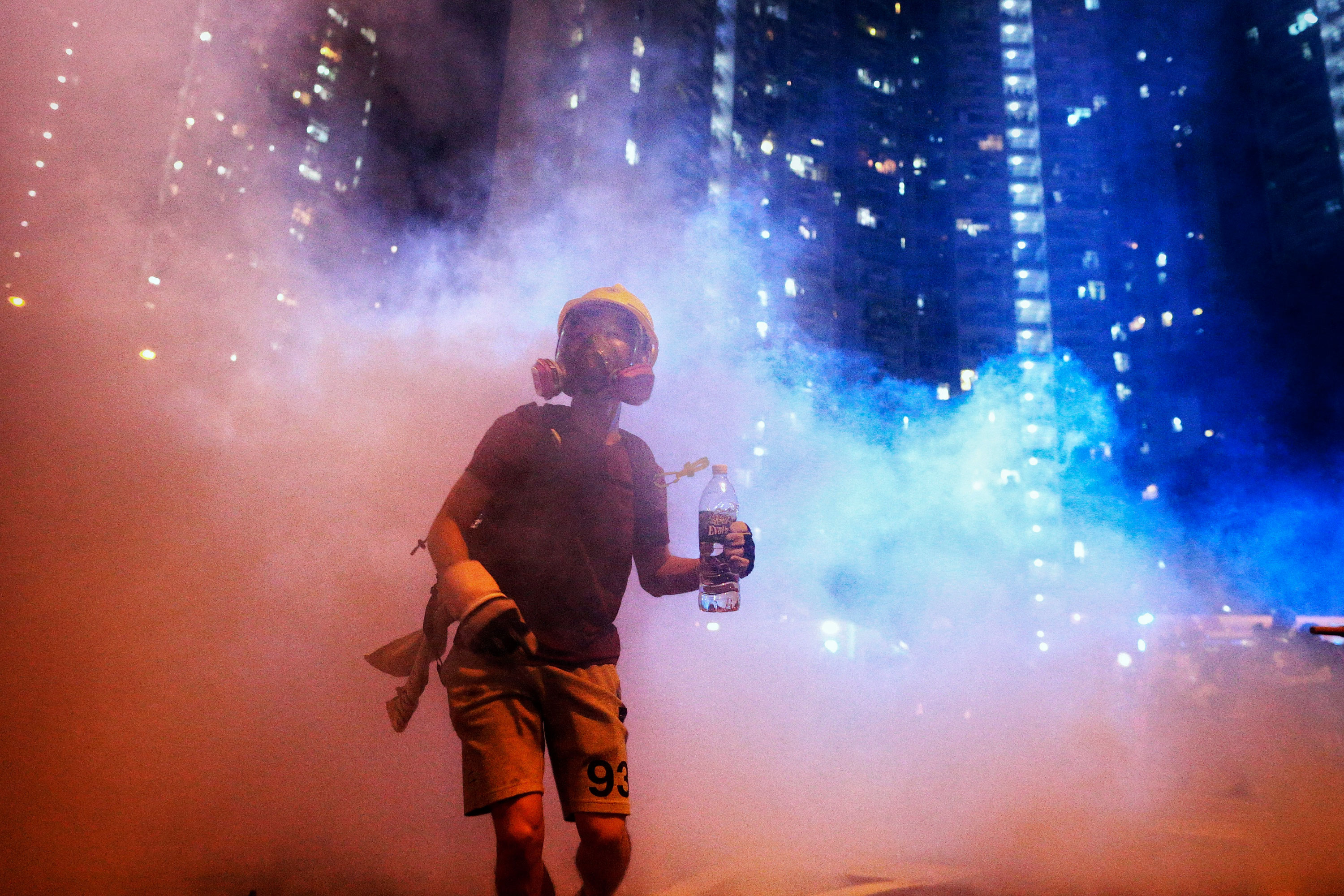 A masked protester walks through clouds of tear gas in Hong Kong. Three months of this protracted tussle have tarnished the image of China, which, at least on paper, espouses a philosophy of peace and tolerance. The communist government's attempts to suppress the unrest are unjust.
