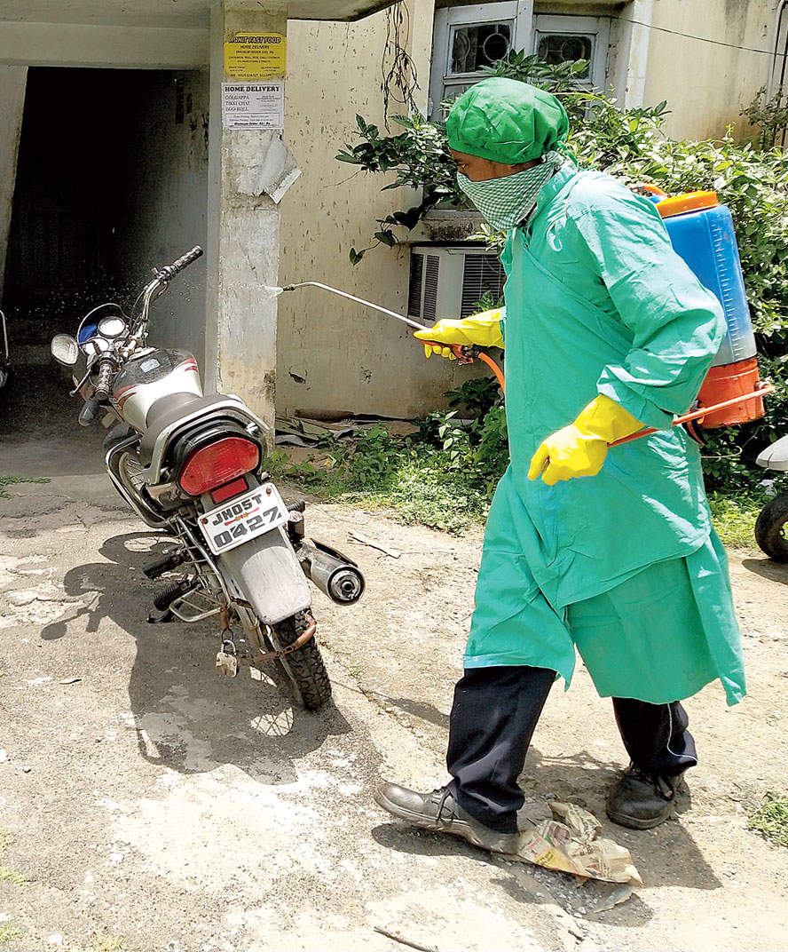 A health worker sprays sanitiser on a bike at a containment zone in Telco, Jamshedpur, on Saturday.
