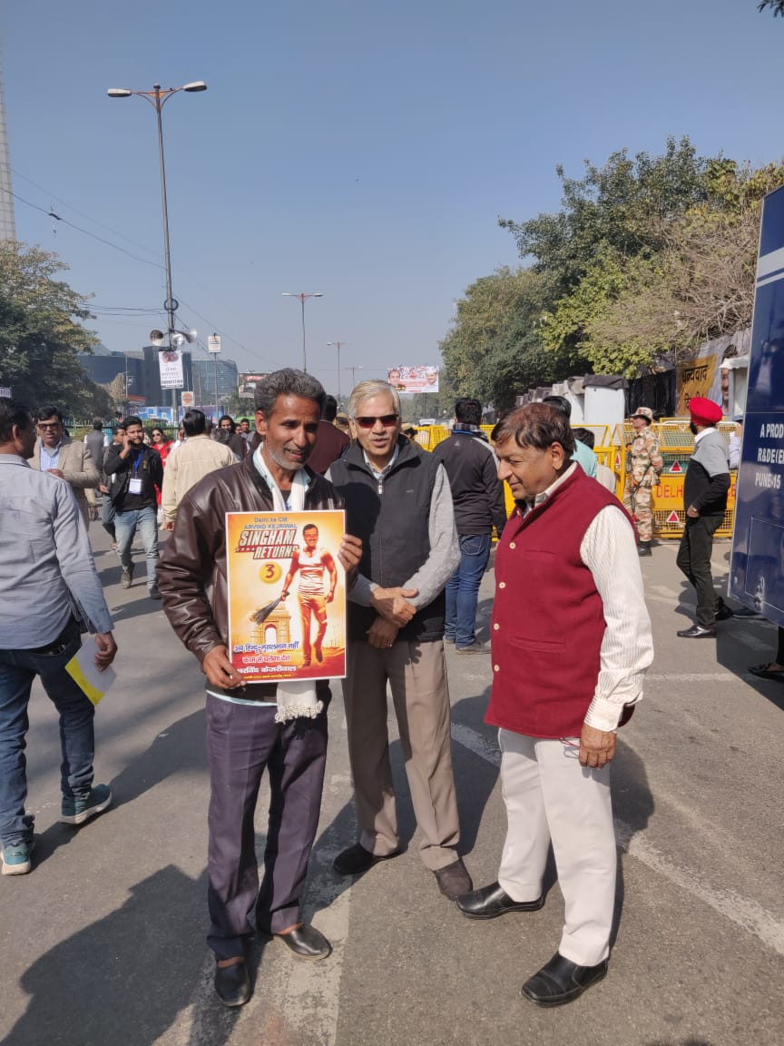A.K. Gupta held a poster showing a muscled up Arvind Kejriwal holding a broom, during the swearing-in ceremony of Delhi chief minister Arvind Kejriwal, at Ramlila Maidan, New Delhi, on Sunday, February 16, 2020.
