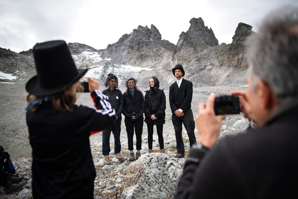 Climate change activists, wearing dark clothing, pose near the 'dying' glacier of Pizol mountain in Wangs, Switzerland, on Sunday
