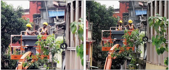 Men on a hydraulic lift use a hammer and (right) a crowbar to raze a damaged building in Bowbazar's Durga Pituri Lane on Tuesday