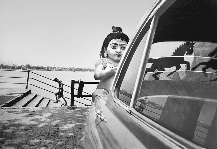 """Ahiritola Ghat. A parked car. A sticker of a horse on the rear windscreen. An idol of Gopal. A man leaving the bathing ghats. """"The horse and the man were counterbalancing each other here,"""" explains Saha. Again there were the horizontal lines of the railing and the stairs in the background."""