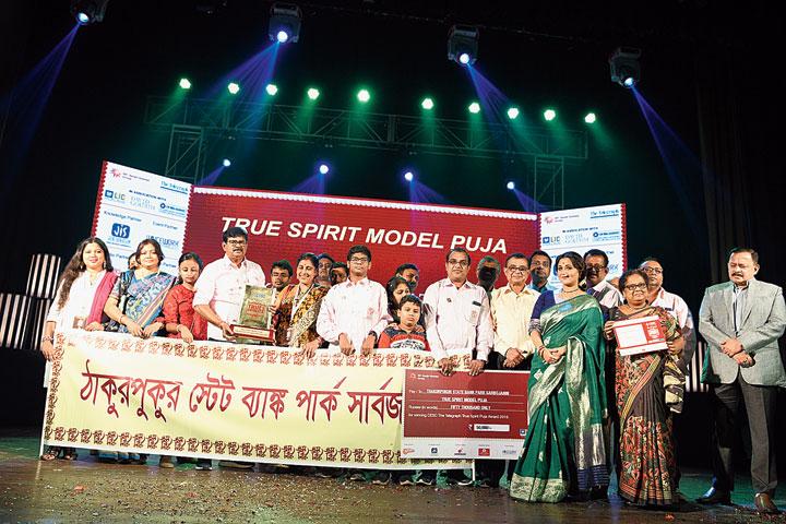 Actress Swastika Mukherjee , DD Purkayastha, managing director & CEO, ABP, and Debasish Banerjee , managing director, distribution, CESC, with members of Thakurpukur State Bank Park Sarbojanin, the Model Puja for CESC The Telegraph True Spirit Puja
