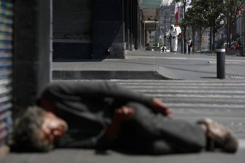 A city worker sprays disinfectant as a man sleeps on the street, in central Mexico City, Monday, April 6, 2020. Mexican President Andres Manuel Lopez Obrador said there will be no huge economic stimulus program as the country faces the threat of coronavirus-induced crisis.