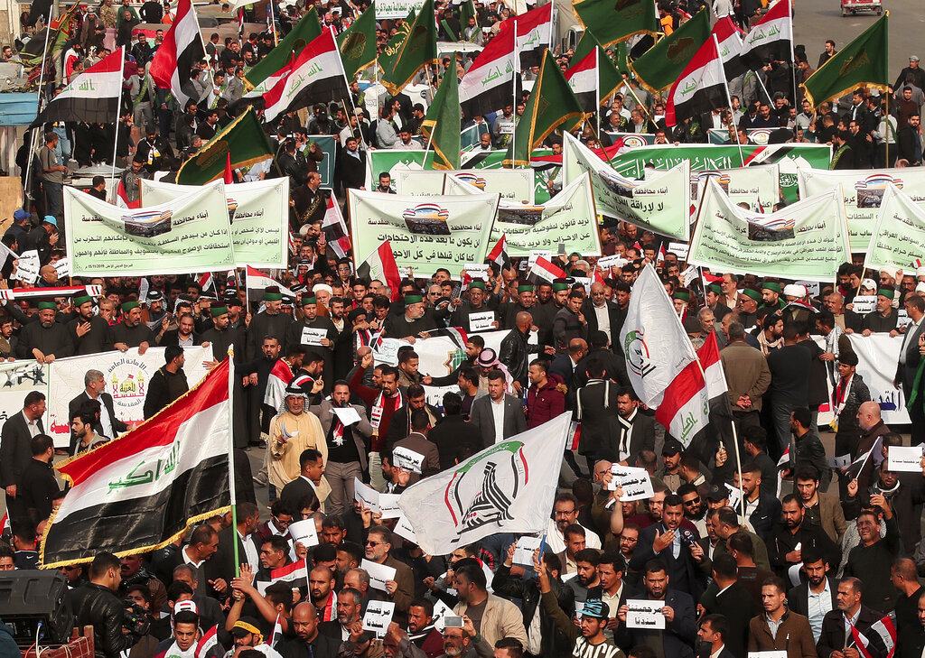 Protesters hold Popular Mobilization forces and Iraqi flags and chanting religious slogans march towards Tahrir Square in Baghdad, Iraq, Friday, December 6, 2019.