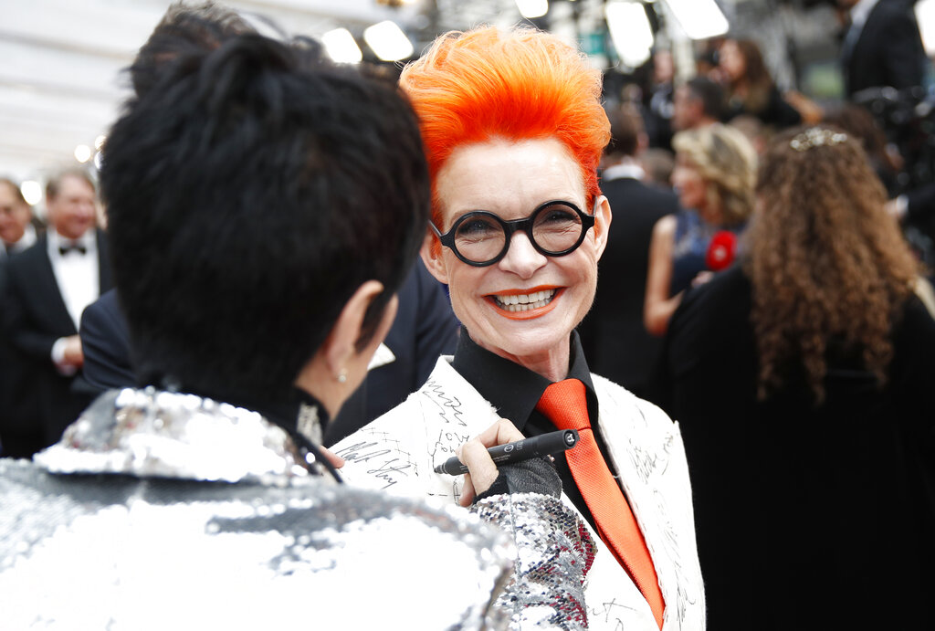 Diane Warren, left, signs Sandy Powell's blazer on the red carpet at the Oscars on Sunday, February 9, 2020, at the Dolby Theatre in Los Angeles
