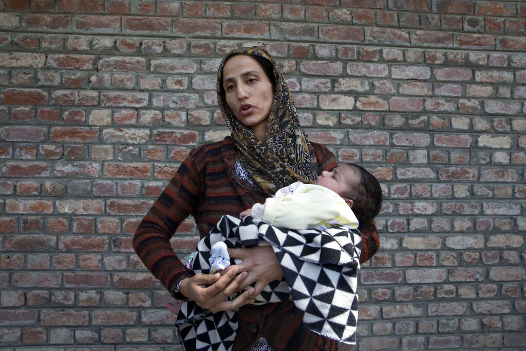 A Kashmiri woman holds her 40-day-old daughter, Tanzeela, as she waits near a police station to hear about her husband who was detained during night raids in Srinagar, on Tuesday, August 20, 2019. Authorities say thousands have been arrested in the communications blackout and security lockdown
