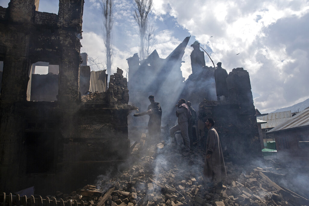 Kashmiri men dismantle a portion of a house destroyed in a gunbattle in Tral village, south of Srinagar, March 4, 2019. The image is part of the photo series that won the 2020 Pulitzer Prize for Feature Photography.