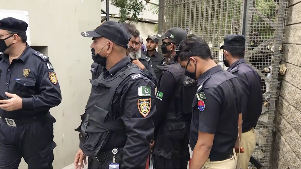 In this image from a video, police stand around an entrance of stock exchange building in Karachi, Pakistan Monday, June 29, 2020.