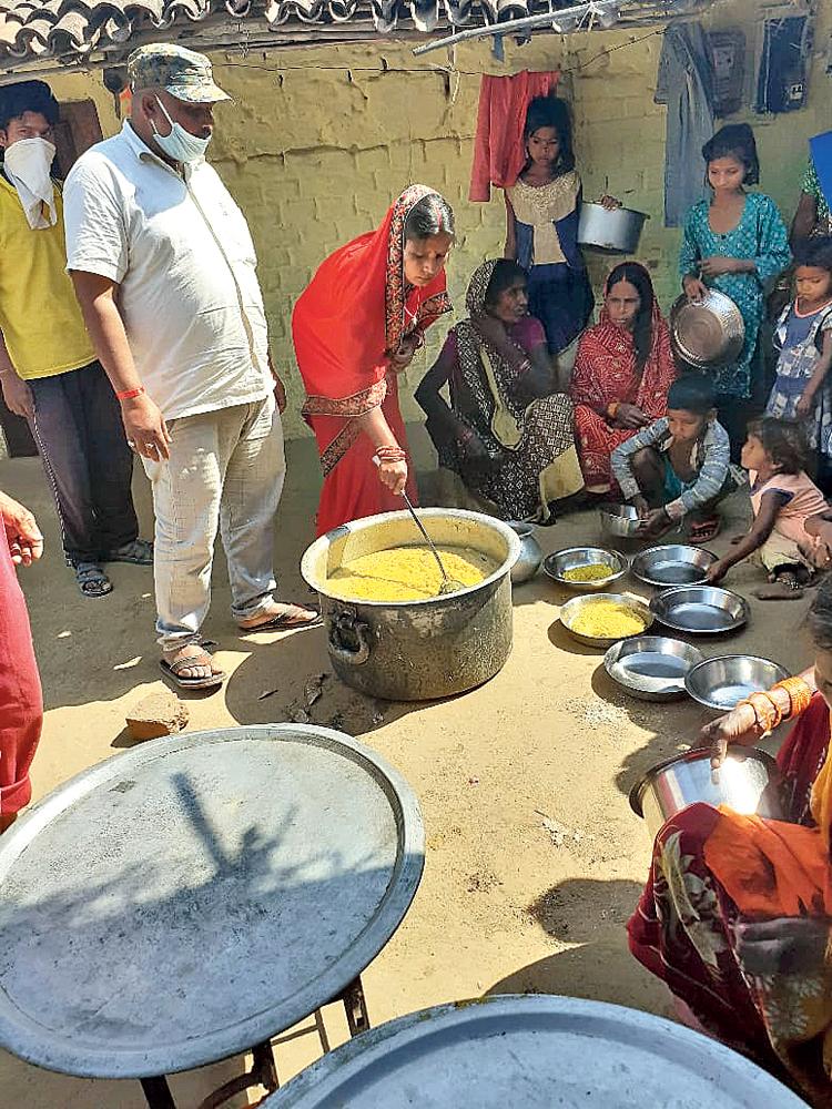 Sanjay Ram and his wife feed the hungry at Kolhuwa village in Palamau on Saturday.