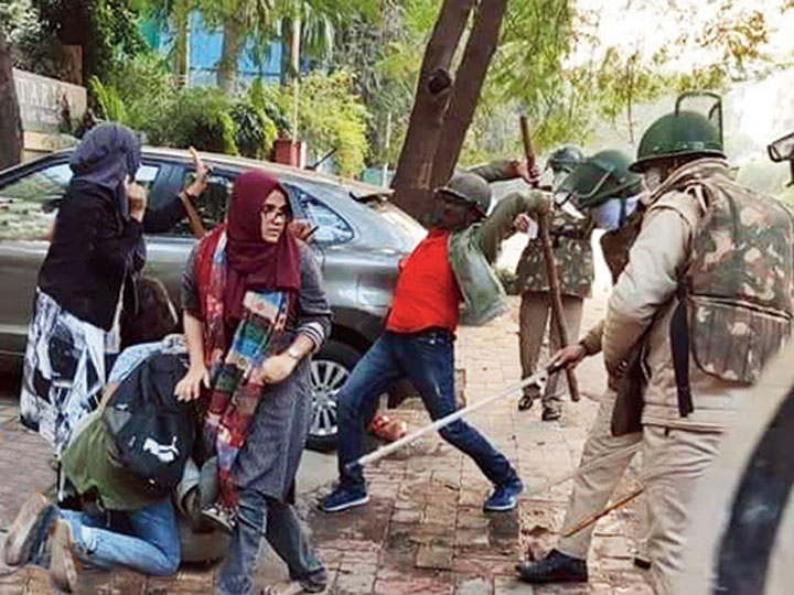 Students of Jamia Millia Islamia defend a male student who was being beaten up by Delhi Police