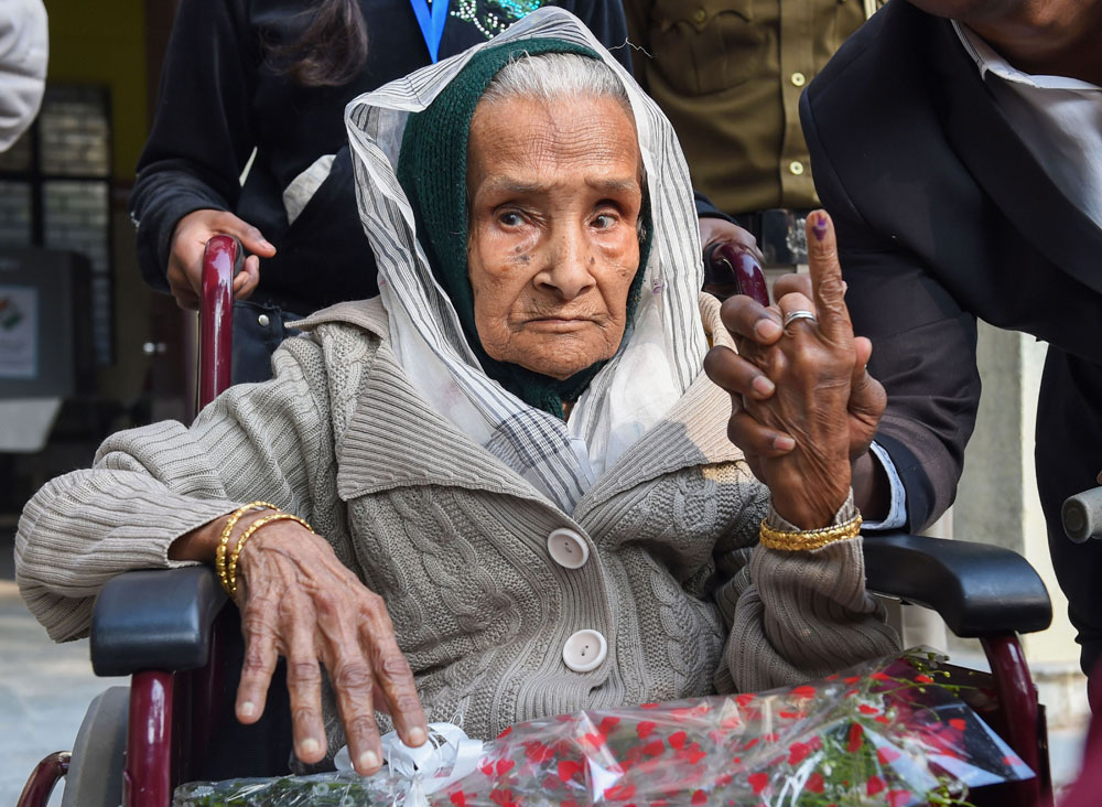 111-year-old Kalitara Mandal shows her finger marked with indelible ink after casting vote during the Delhi Assembly elections at Chittaranjan Park polling station, in New Delhi