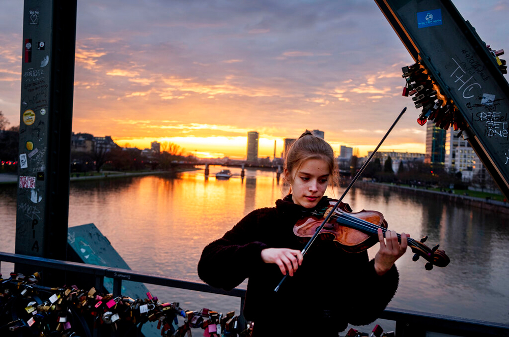 A woman plays the violin on a pedestrian bridge over the river in Frankfurt, Germany, on December 19