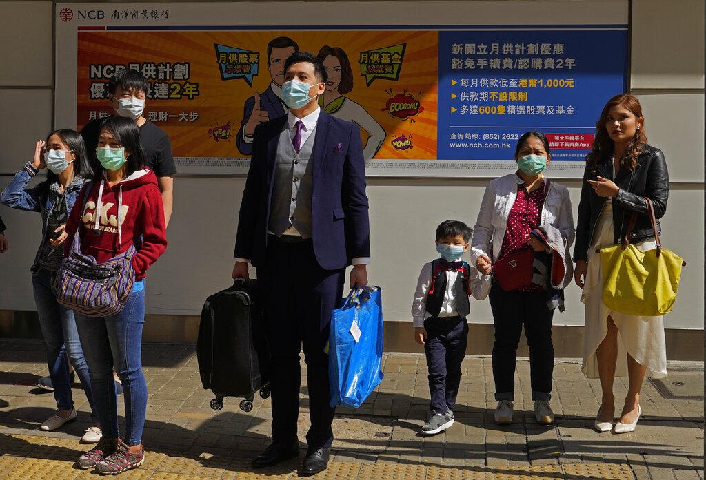 People wearing face masks wait at a pedestrian cross walk Hong Kong on Saturday, February 22, 2020