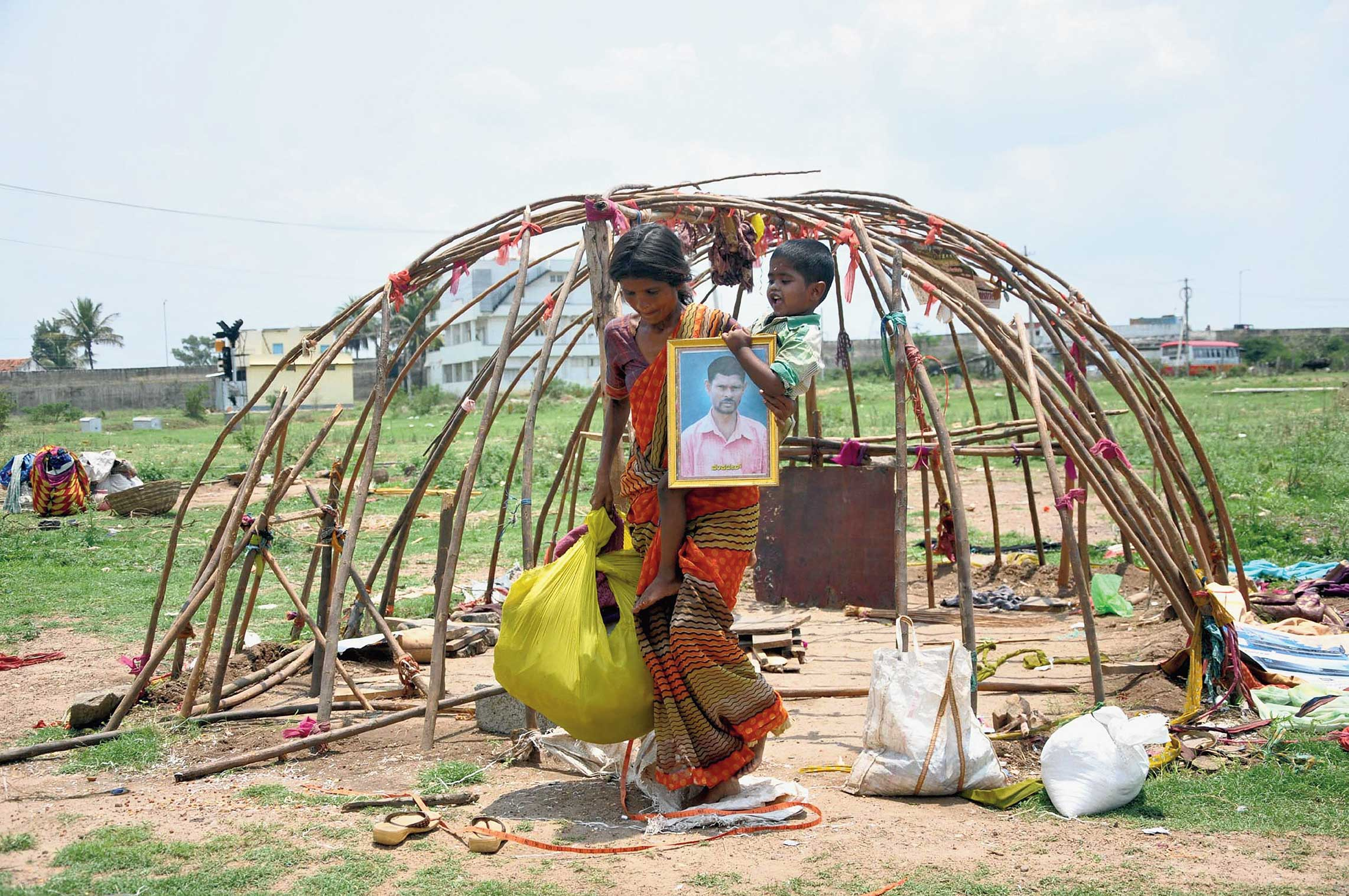 A migrant worker vacates her makeshift tent in Chikmagalur, Karnataka, on Wednesday as she prepares to leave for home with her child and her belongings.