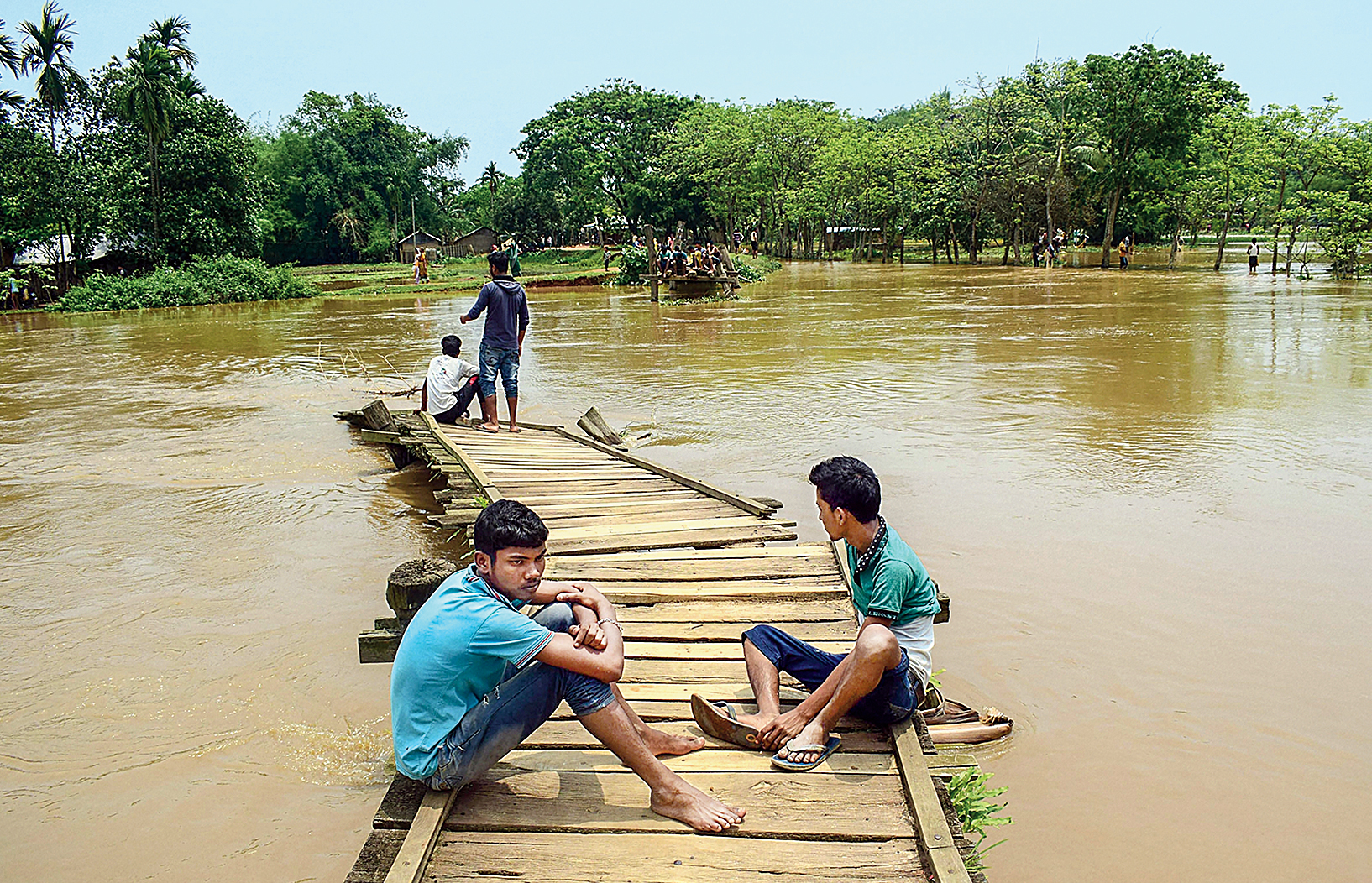 Young boys sit on a wooden bridge over swollen Singra river, following heavy rainfall induced by Cyclone Fani, at Boko in Kamrup district.