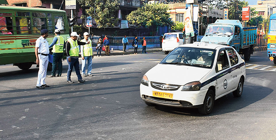Traffic offenders regulate traffic in the company of a policeman at Birati More on Jessore Road.