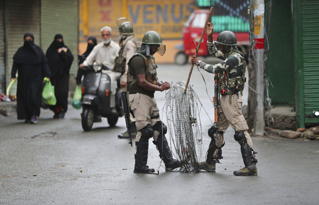 Paramilitary soldiers prepare to close off a street with barbwire in Srinagar
