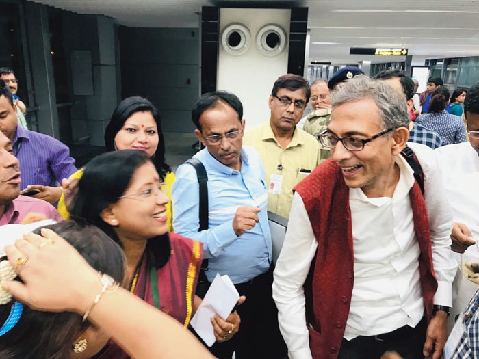 Airport officials greet Abhijit Banerjee after he landed in Calcutta by an IndiGo flight from Delhi. Behind Banerjee is gastroenterologist Abhijit Chowdhury (blue shirt), who was on the same flight. Chowdhury heads the NGO Liver Foundation that works for the improvement of rural health care and collaborates with Banerjee in his research