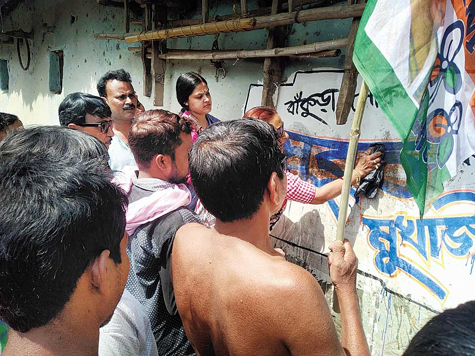 A Trinamul graffiti, which party workers claimed had been smeared with cow dung, being cleaned in Bankura.