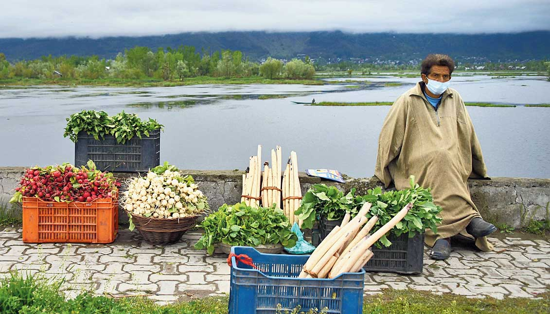 A vegetable vendor sits by the Dal Lake as he waits for customers  in Srinagar on Saturday.