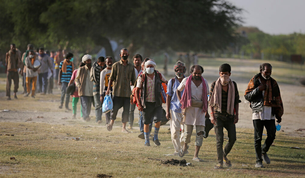 Indian migrant laborers and homeless people walk towards a bus as they are being evicted from the banks of Yamuna River where they have been squatting during lockdown in New Delhi, Wednesday, April 15, 2020.