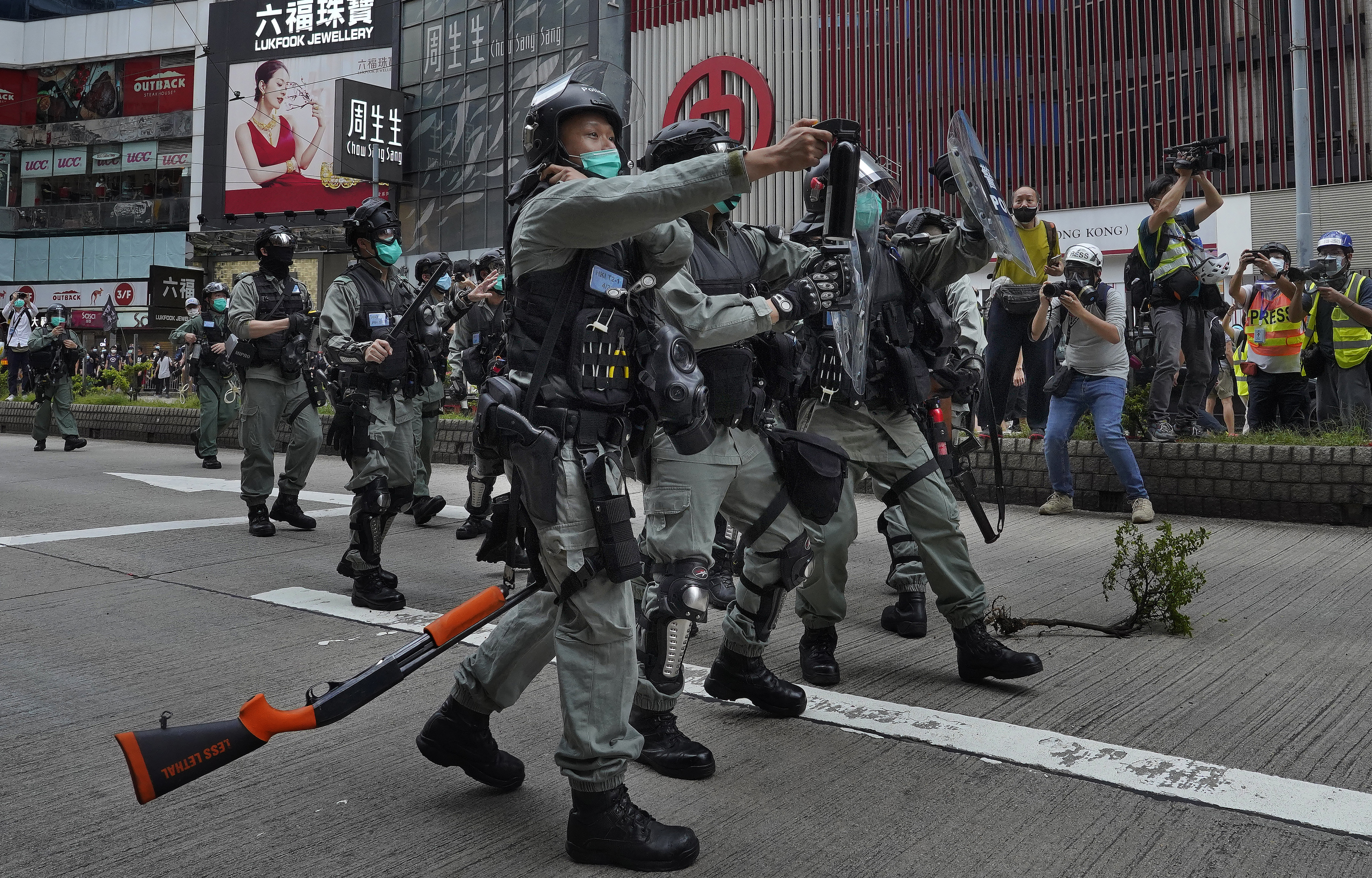 Riot police use pepper spray on protesters as one drops his gun during a demonstration in Hong Kong