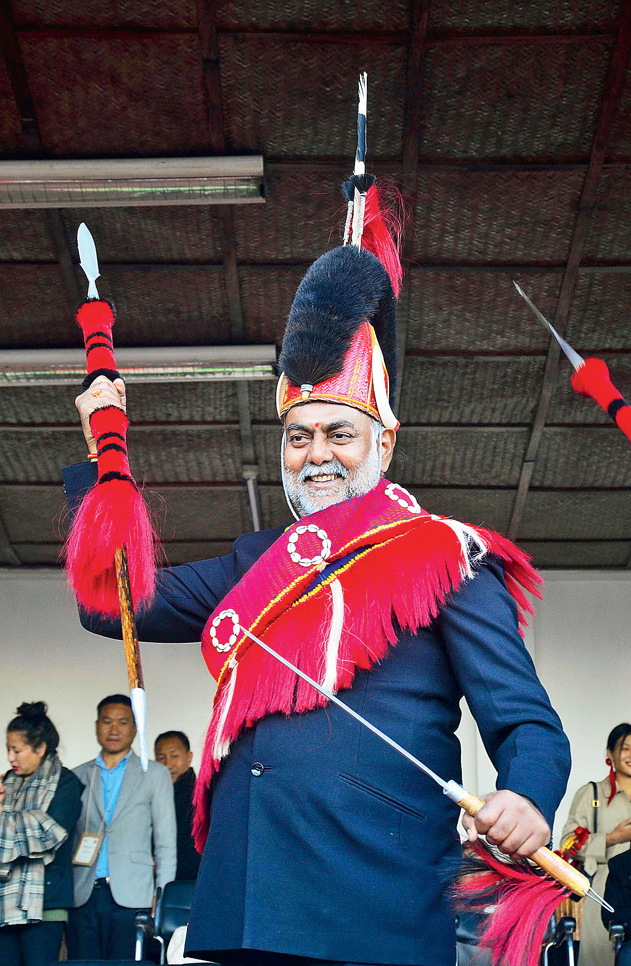 Prahlad Singh Patel wears the traditional Naga attire presented to him on the fourth day of the annual Hornbill festival, at Kisama near Kohima, on Wednesday.