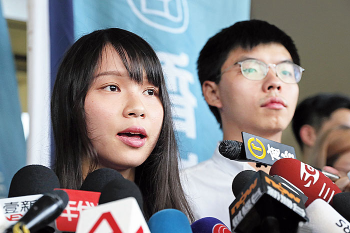 Pro-democracy activists Agnes Chow and Joshua Wong speak to reporters outside a court in Hong Kong on Friday