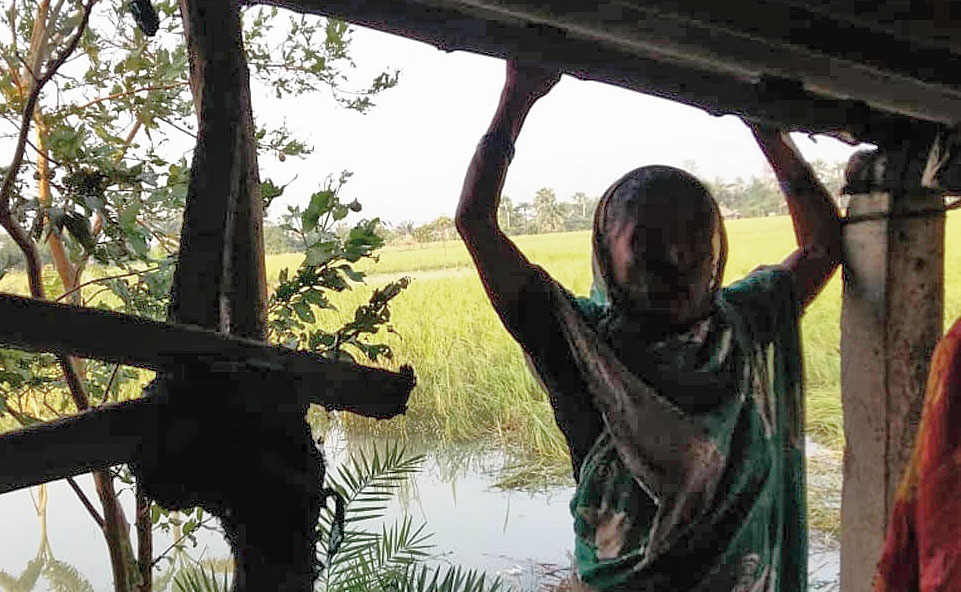 Parijan Bibi standing in front of a house whose wall was blown away by Cyclone Bulbul.
