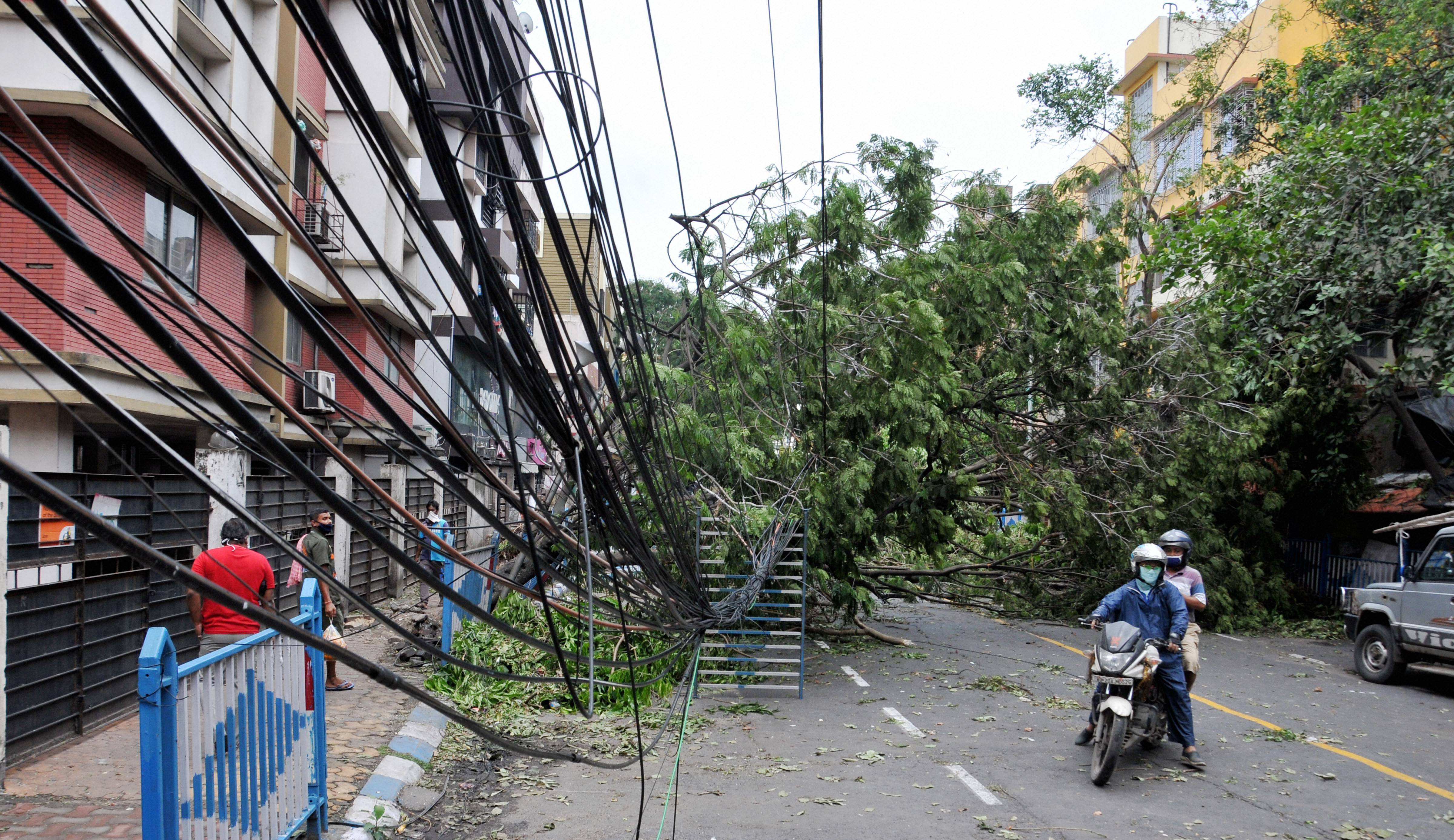 Damaged electric cables hang close to a street after trees fell on it, in the aftermath of Cyclone Amphan, in Kolkata, Friday, May 22, 2020