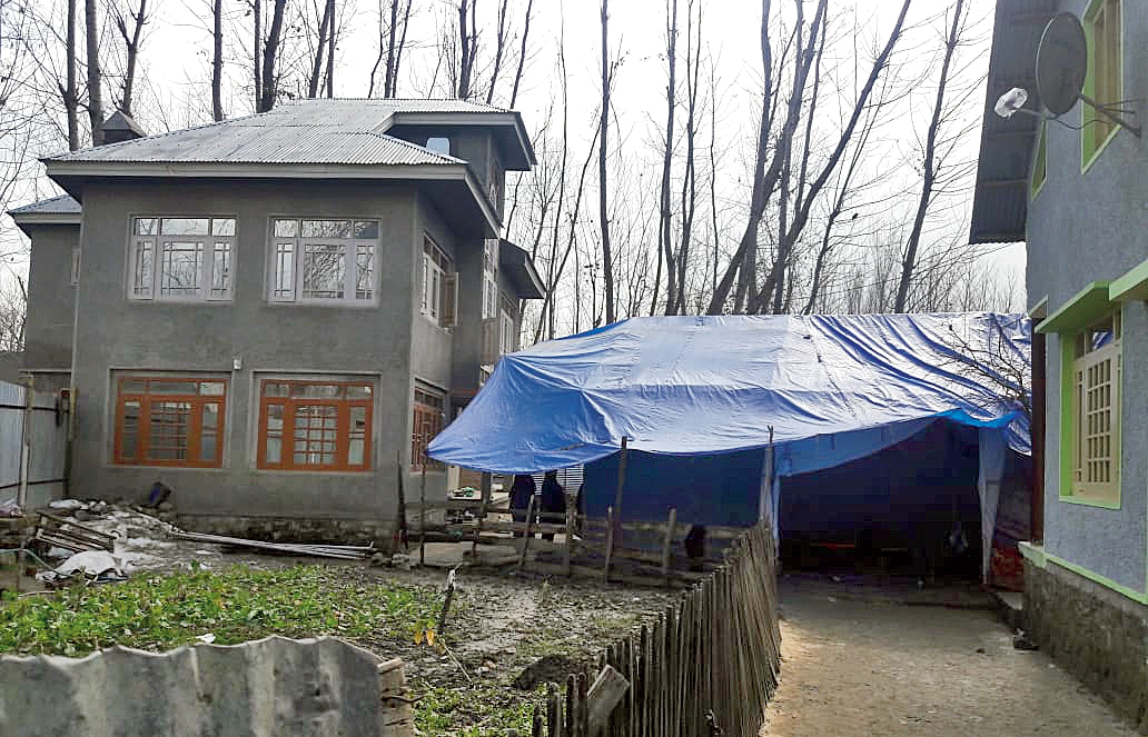 A tent has come up on the lawns of Adil Ahmad Dar's home at Gundhibagh in Pulwama to receive mourners.