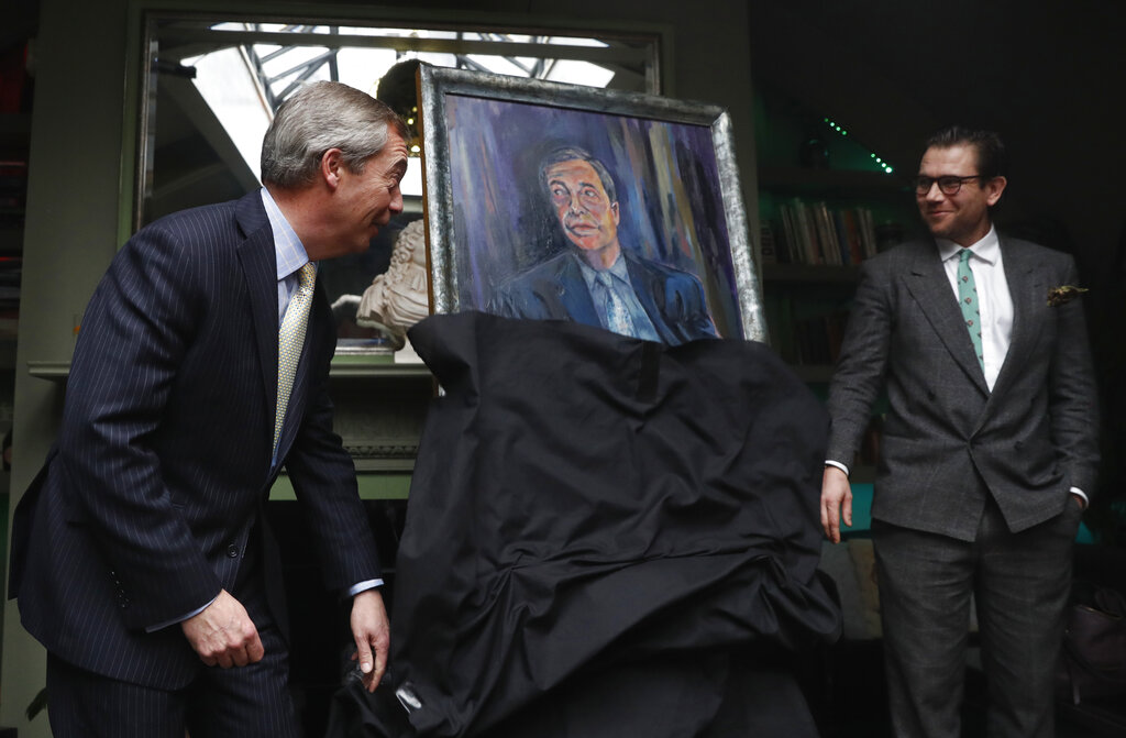 Brexit Party leader Nigel Farage, left, unveils a portrait of himself with the artist Dan Llywelyn Hall at right, in London, on Thursday. The painting is to be sold in aid of a charity that looks after military veterans.