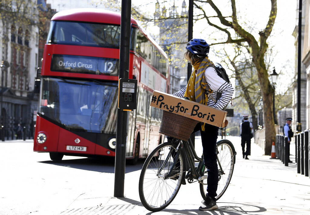 A woman shows a sign on her bicycle as British Prime Minister Boris Johnson is in intensive care fighting the coronavirus in London, Tuesday, April 7, 2020.