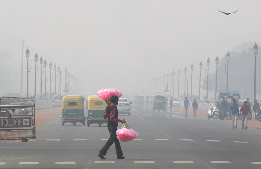 A candy floss vendor looks for customers in a thick smog in New Delhi on Tuesday, November 12, 2019.