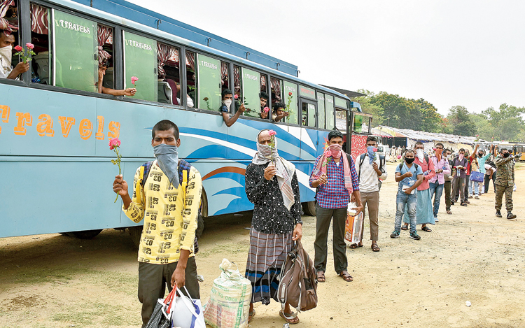 Migrant workers from Kerala stand in a queue to board buses to reach their native places after arriving in Dhanbad