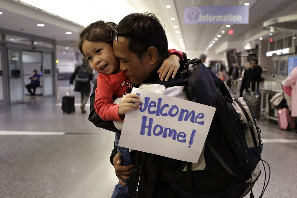 Thy Chea, of Lowell, Massachusetts, center right, originally of Cambodia, hugs his daughter on his arrival at Boston's Logan Airport, Wednesday, February 26, 2020, after getting his green card reinstated last year. Chea is the fourth Cambodian refugee to be allowed back into the country after being deported, and just the first on the East Coast, according to Asian American organizations that have been fighting increased deportations of Southeast Asians under President Donald Trump.