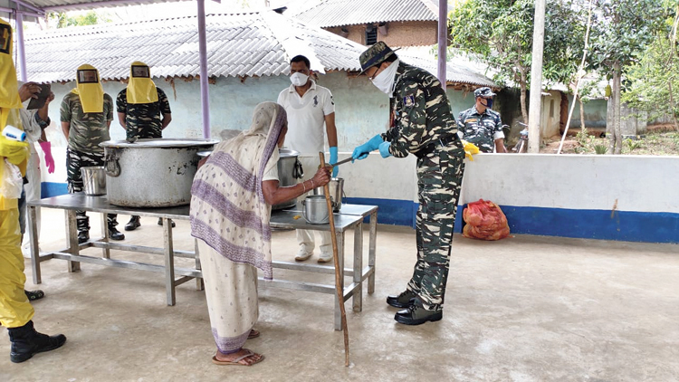 CRPF personnel provide cooked meals to an elderly woman in Jhargram