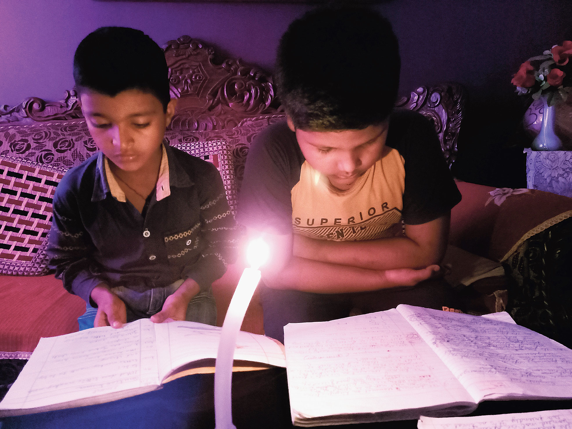 Children are forced to study in candlelight during a power cut in Kokar, Ranchi, last week.