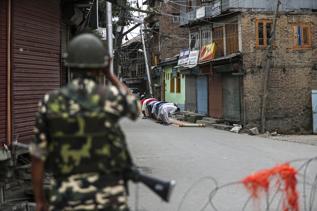 A paramilitary soldier stands guard as Kashmiri Muslims offer Friday prayers on a street outside a local mosque during curfew like restrictions in Srinagar, August. 16, 2019. The image is part of the photo series that won the 2020 Pulitzer Prize for Feature Photography.
