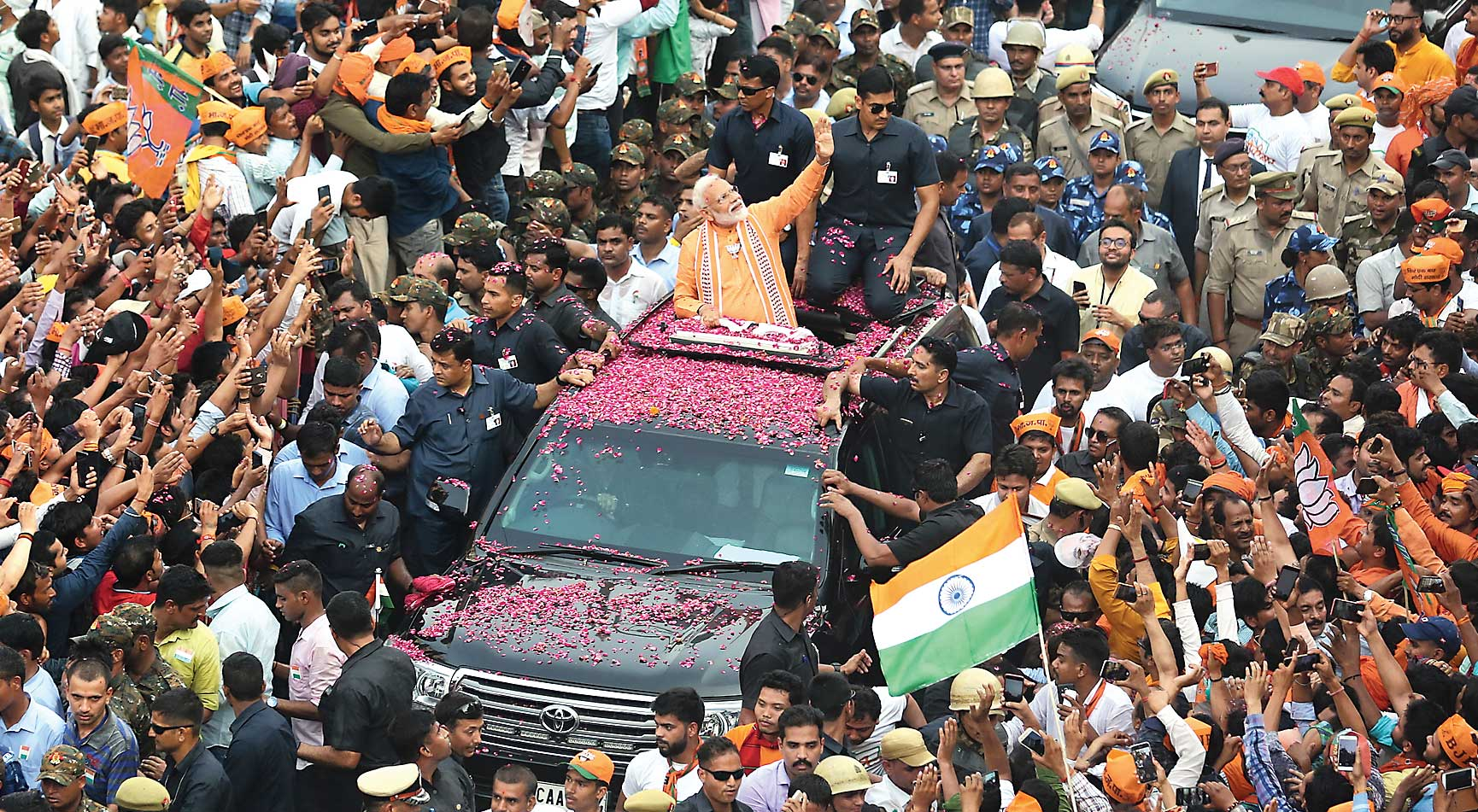 Prime Minister Narendra Modi waves to the crowd during a political campaign road show in Varanasi, on Thursday.