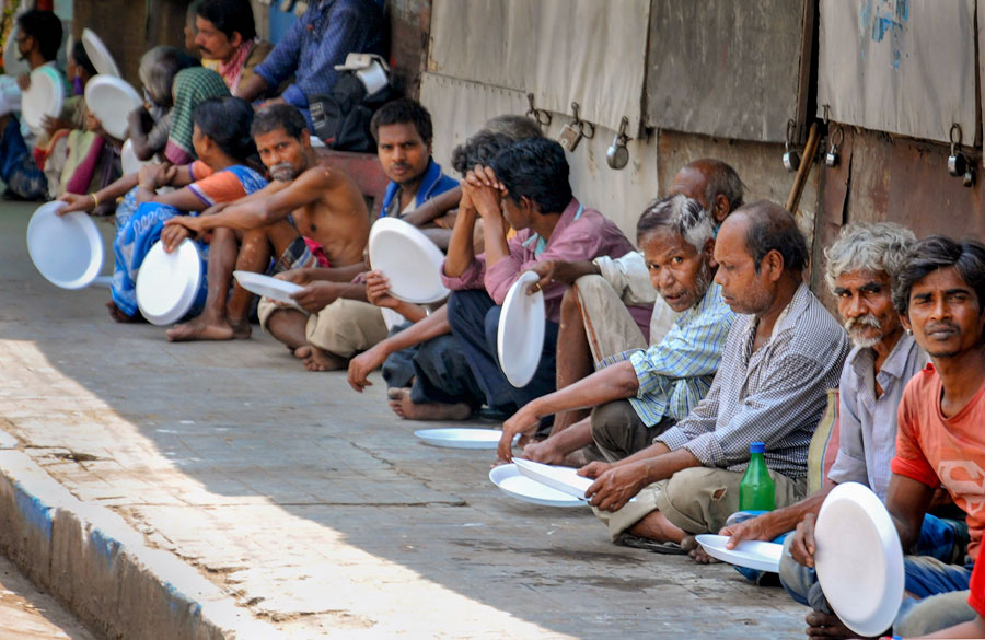 People wait to receive free food distributed by volunteers, during the nationwide lockdown to curb the spread of coronavirus, in Calcutta on Monday