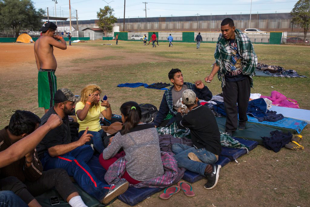 Central American migrants, with the border fence that divides Mexico and the US as a background, gather after breakfast at a temporary shelter in Tijuana, Mexico, Friday, November 16, 2018.