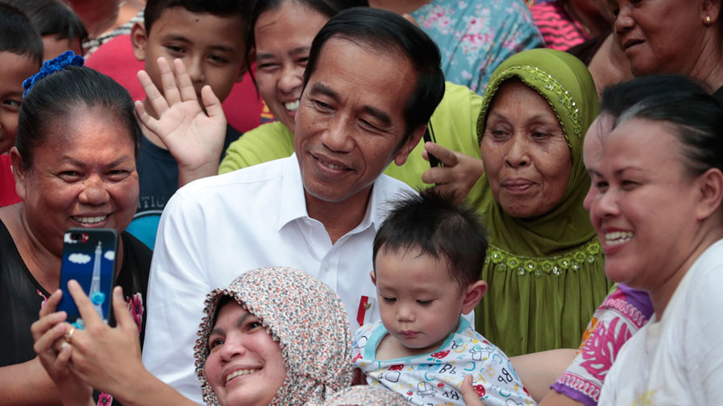 People take selfies with Joko Widodo in a slum in Jakarta on May 21, 2019. Ever since he got re-elected as Indonesia's president last month, his focus has been on development