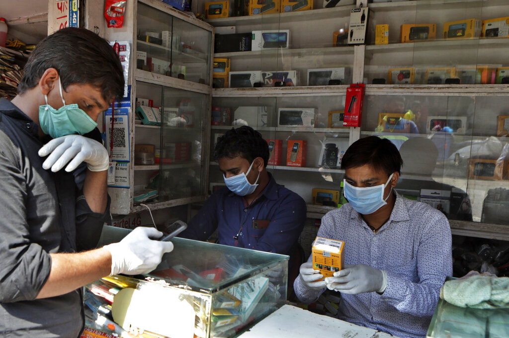 Mobile vendors wear protective masks and gloves as a precaution against coronavirus at their outlet in Mumbai, Tuesday, March 17, 2020.