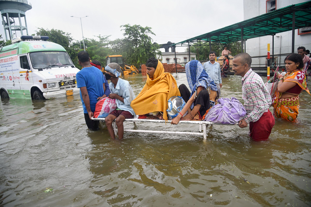Patients are shifted from the flooded Nalanda Medical College and Hospital in Patna on Saturday