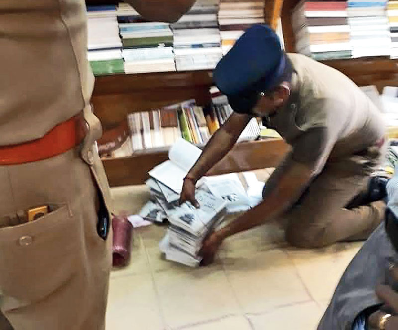 A policeman collects copies of the book from the Chennai bookshop